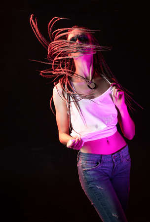 Emotional photo of a beautiful slim girl with creative make-up and a hairstyle of cornrows, wearing white t-shirt, dancing waves her braids on a black. Conceptual, commercial, advertising design. Фото со стока