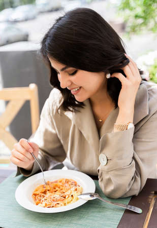 Beautiful smiling brunette girl having lunch in a street cafe, sitting at a table and eating Italian pasta. Advertising, commercial design. Copy space.