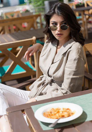Beautiful smiling brunette girl wearing sunglasses is having lunch in a street cafe, sitting at a table and eating Italian pasta and drinking coffee. Advertising, commercial design. Copy space.