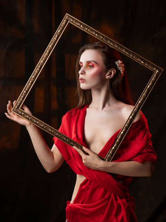 Beautiful girl with trendy makeup, wearing a silk scarf thrown over her shoulders that covers her naked breast, holds picture frame on the background of the shadow from the window. Stock Photo