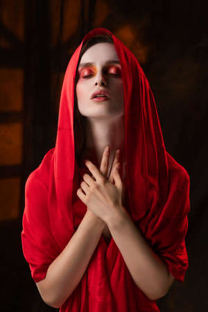 Beautiful girl with fashionable makeup in red tones, wearing a red silk scarf thrown over her head that covers her naked breast, sensually poses on the background of the shadow from the window.