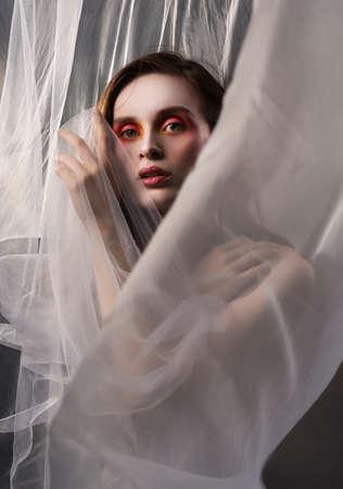 Una bella ragazza snella posa tra il tessuto bianco di un velo che svolazza al vento e che copre la sua nudità. Foto artistica, concettuale, sfocata