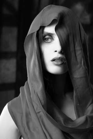 Beautiful girl with fashionable makeup, wearing a silk scarf thrown over her head that covers her naked breast, sensually poses on the background of the shadow from the window. Black and white.