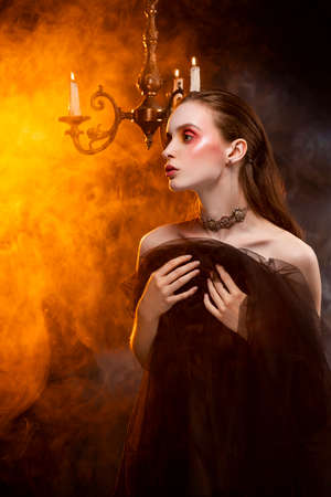 A beautiful slim girl, wearing earrings and a necklace, and covering her with a black veil, sensually poses in theatrical smoke near the chandelier with lightning candles