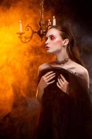 Ein schönes schlankes Mädchen, das Ohrringe und eine Halskette trägt und sie mit einem schwarzen Schleier bedeckt, posiert sinnlich im Theaterrauch in der Nähe des Kronleuchters mit Blitzkerzen