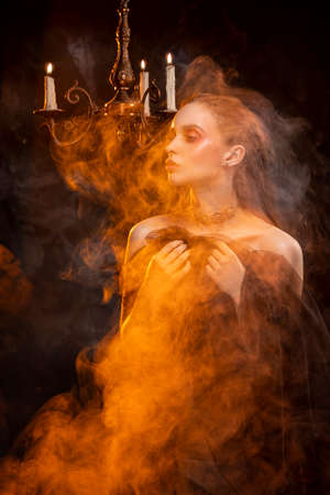 A beautiful slim topless girl, wearing earrings and a necklace, and covering her nudity with a black veil, sensually poses in theatrical smoke near the chandelier with lightning candles Stock Photo