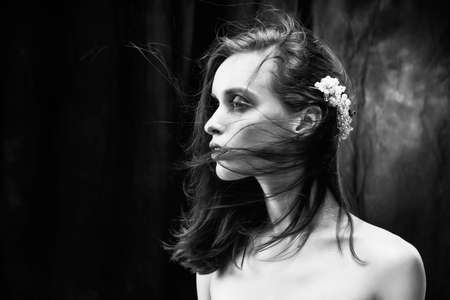 A beautiful slim girl with naked shoulders and fashionable red makeup, wearing jewelry in her hair, sensually poses while the wind blows her hair. Close Up monochrome black and white photo
