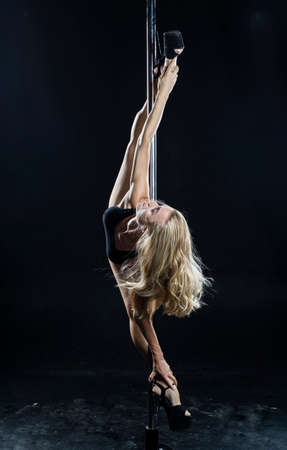 Beautiful athletic busty elegant blonde girl performs artistic elements of an exotic dance on a black background. Health, lifestyle, sports design. Copy space Stockfoto