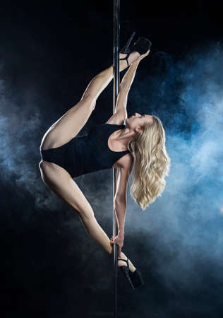 Beautiful athletic busty elegant blonde girl performs artistic elements of an exotic dance in a theatrical smoke. Health, lifestyle, sports design. Copy space Stockfoto