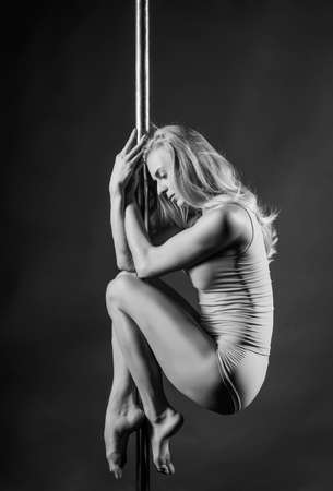 Beautiful athletic busty elegant blonde girl performs artistic elements of an exotic dance on a gray background. Health, lifestyle, sports black and white monochrome design. Copy space
