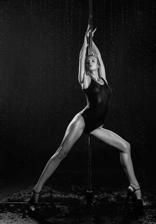 Beautiful wet athletic busty elegant blonde girl performs artistic elements of an exotic dance on the rain. Health, lifestyle, sports, black white monochrome design. Copy space