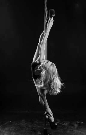 Beautiful athletic busty elegant blonde girl performs artistic elements of an exotic dance on a black background. Health, lifestyle, sports monochrome design. Copy space