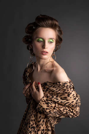 A beautiful topless girl wearing a stockings, large earrings and an unbuttoned leopard blouse elegantly sits on a stool. Fashionable, advertising design.