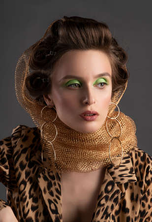 A beautiful topless girl wearing a golden net on her hair, stockings, large earrings and an unbuttoned leopard blouse elegantly sits on a stool. Fashionable, advertising design