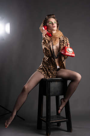 A beautiful topless girl wearing a golden net on her hair, stockings, large earrings and an unbuttoned leopard blouse sits on a stool and holds red vintage phone. Fashionable, advertising design