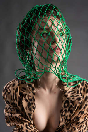 A beautiful topless girl wearing a green net on her head, stockings, large earrings and an unbuttoned leopard blouse poses on gray background. Fashionable, advertising design