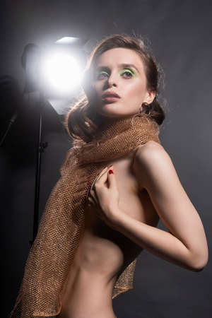 A beautiful topless girl wearing golden net scarf poses, holding her hands on her naked breasts at the lamp on a gray background. Fashionable, advertising design