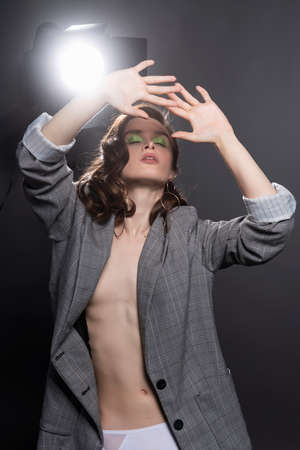 A beautiful topless girl wearing a gray unbuttoned oversized jacket, white panties and stockings poses at the lamp on a gray background. Fashionable, advertising design