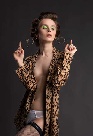 A beautiful topless girl wearing a stockings, and an unbuttoned leopard blouse pulls earrings with her fingers. Fashionable, advertising design