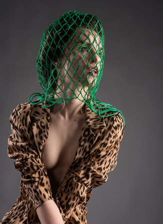 A beautiful girl wearing a green net on her head, stockings, large earrings and an unbuttoned leopard blouse poses on gray background. Fashionable, advertising design