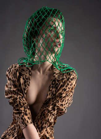 Una hermosa niña con una red verde en la cabeza, medias, pendientes grandes y una blusa de leopardo desabrochada posa sobre fondo gris. Diseño publicitario de moda