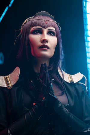 A beautiful busty cosplay girl wearing an erotic leather costume sensually cries with tears in her face and makes a praying gesture on a dark background in blue light. Close up portrait Фото со стока