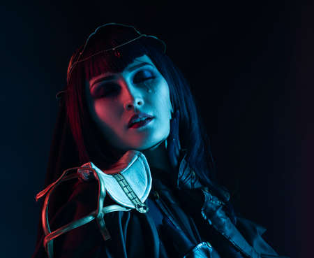 A beautiful busty cosplay girl wearing an erotic leather costume sensually cries with tears in her face on a dark background in red and blue lights. Close up portrait Фото со стока