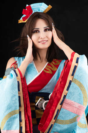 Beautiful smiling leggy busty cosplay girl wearing a stylized Japanese kimono costume cheerfully posing on a black background. Close up portrait