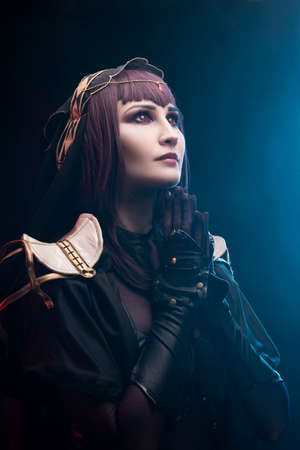 A beautiful busty cosplay girl wearing an leather costume sensually cries with tears in her face and makes a praying gesture on a dark background in blue light. Close up portrait