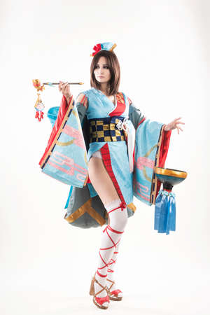 Beautiful leggy busty cosplayer girl wearing a stylized Japanese kimono costume cheerfully posing holding a fake pipe in the wind. Isolated on a white background