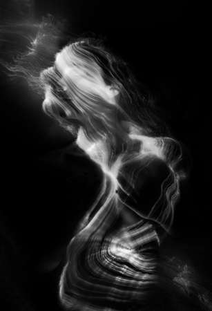 Conceptual monochrome black and white avant-garde portrait of a beautiful young girl covered with lines applied by a light brush. Art style creative photo. Advertising, fashion and commercial design Stock fotó