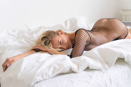Beautiful nude slender blonde girl, wearing sexy black bodystocking, sensually laying with her buttocs up on the bed in a white room. Fashionable, advertising and commercial design Banque d'images