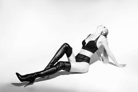 A beautiful slender leggy blonde model girl wearing sexy black lingerie and high heel leather boots lays on the white floor. Fashionable, monochrome, advertising and commercial design