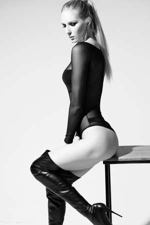A beautiful slender leggy blonde model girl wearing sexy black body and high heel leather boots sits on the stool at the white wall. Fashionable, monochrome, advertising and commercial design Banco de Imagens