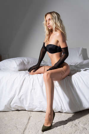 Beautiful slender blonde girl with nude makeup wearing sexy black lingerie and a gloves, sensual posing on the bed in a white room. Fashionable, advertising and commercial design
