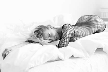 Beautiful nude slender blonde girl, wearing sexy black bodystocking, sensually laying with her buttocs up on the bed in a white room. Fashionable, monochrome, advertising and commercial design Stockfoto
