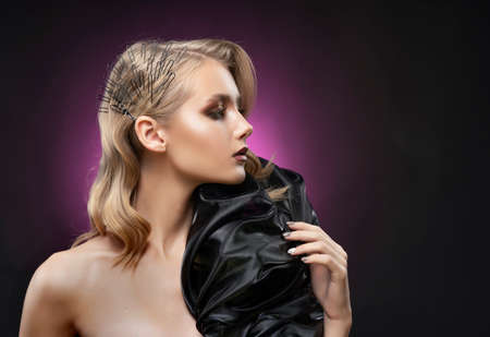 Beautiful blonde young girl with trendy hairstyle covering her breasts with a large black fabric bow, poses on black and violet background. Clear, healthy skin. Advertising, commercial design