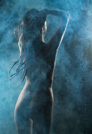 Beautiful slim wet nude girl, posing in the drops of the rain, in theatrical smoke, sensually touching and washing her passionary body on dark background. Artistic design