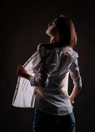 Beautiful slim girl wearing jeans and an open shirt posing. The light shines through her clothes and the silhouette of her body is visible. Creative, conceptual design