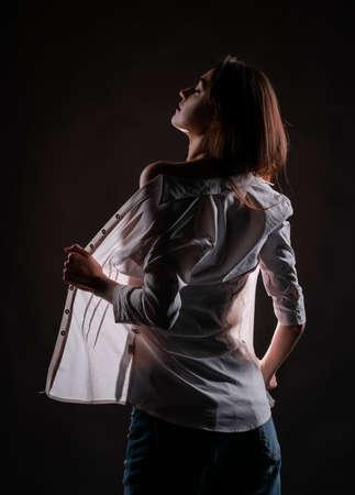 Hermosa chica delgada con jeans y una camisa abierta posando. La luz brilla a través de su ropa y la silueta de su cuerpo es visible. Diseño creativo y conceptual Foto de archivo