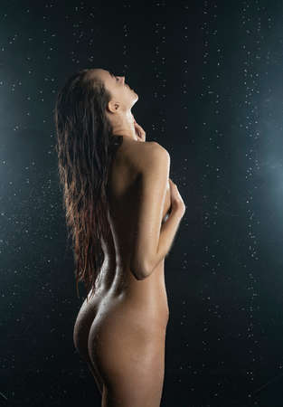 Beautiful slim nude girl, with healthy wet body sensually posing in the rain showing her nice butt and back on black background. Artistic design Stock Photo
