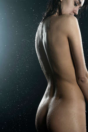 Beautiful slim nude girl, with healthy wet body sensually posing in the rain showing her nice butt and back on black background. Artistic design Stock fotó