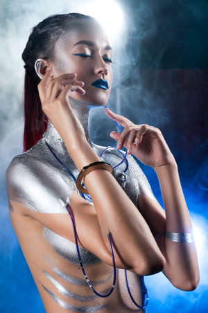 A beautiful slender topless cyborg girl with a body covered in silver paint, with tubes of blue liquid stuck in her skin, posing with handcuffs in the smoke. Conceptual, creative, art design