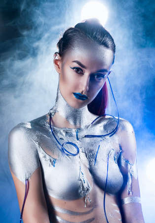 A beautiful slender topless cyborg girl with a body covered in silver paint, with tubes of blue liquid stuck in her skin, poses in the smoke. Creative, conceptual, fantasy design. Close up Stockfoto
