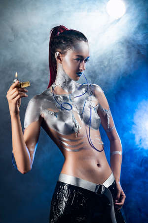 A beautiful slender topless cyborg girl with a body covered in silver paint, with tubes of blue liquid stuck in her skin and handcuffs on her arm, posing with a lighter in the smoke. Creative design