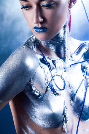 A beautiful slender cyborg girl with a body covered in silver paint, with tubes of blue liquid stuck in her skin, poses in the smoke. Creative, conceptual, fantasy design. Close up