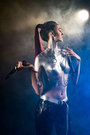 A beautiful slender topless cyborg girl with a body covered in silver paint, with tubes of blue liquid stuck in her skin and handcuffs on her arm, posing with a gun in the smoke. Creative, art design Banco de Imagens