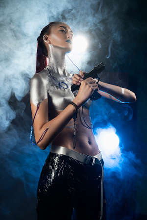 A beautiful slender topless cyborg girl with a body covered in silver paint, with tubes of blue liquid stuck in her skin and handcuffs on her arm, posing with a gun in the smoke. Creative, art design Stockfoto