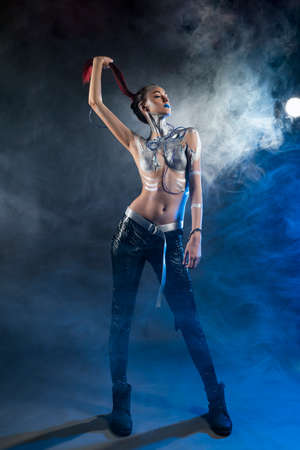 A beautiful slender topless cyborg girl with a body covered in silver paint, with tubes of blue liquid stuck in her skin and handcuffs on her arm, pulls her hair in the smoke. Creative design