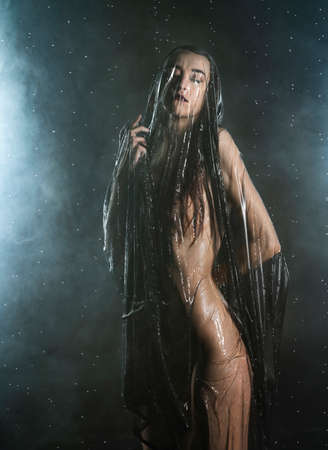 Beautiful slim wet girl, sensually posing nude in the rain, in theatrical smoke, with her body covered with black transparent veil on dark background. Art, conceptual, fashionable design